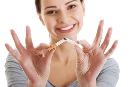 Young beautiful woman holding broken cigarette in front  Isolated on white