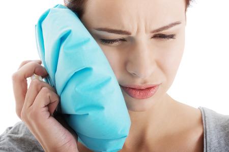 歯痛と氷の袋を持つ若い女性。白で隔離されます。 写真素材