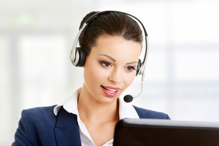 Mooie jonge call center medewerker lachend, geïsoleerd op wit