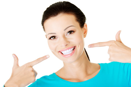 Beautiful woman pointing on her perfect white teeth. Isolated on white.