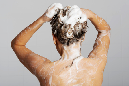 Mujer que toma una ducha y champú cabello