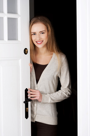 美しい白人女性のドアのそばに立って、それらを開きます。