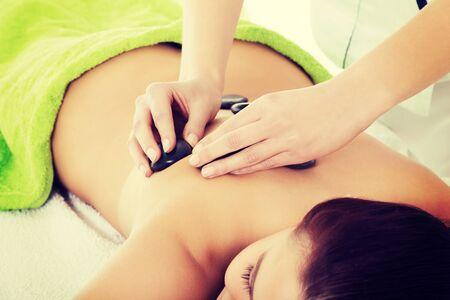 Beautiful woman lying on spa salon having stone massage. Spa concept. Stock Photo - 29176632