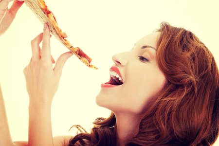 Happy woman eating tasty pizza.