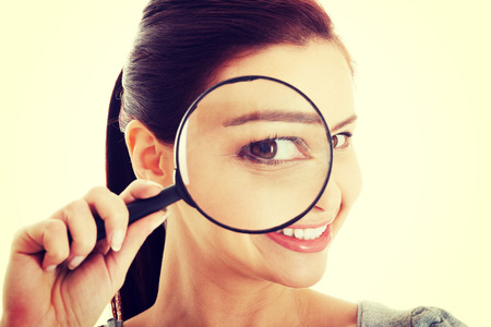 Young beautiful woman with magnifying glass