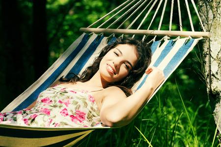 Young woman lying in a hammock in garden