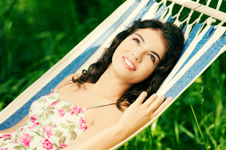 Young woman lying in a hammock in garden photo