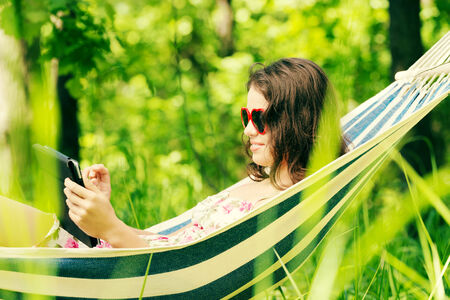 Young woman lying in a hammock in garden with E-Book on tablet computer. photo