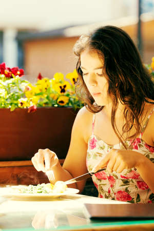 casualness: Young summer woman eating dinner in restaurant.