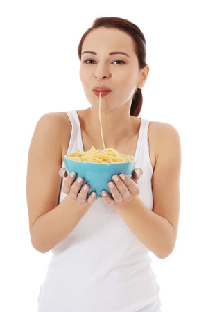 Beautiful woman eating pasta from a bowl. 版權商用圖片