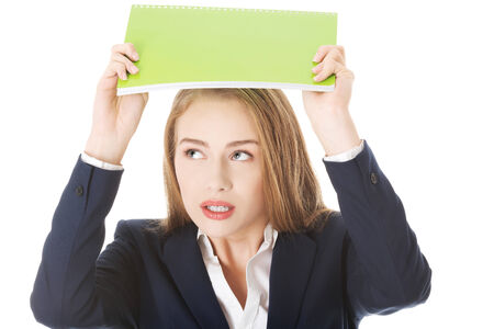 Beautiful caucasian woman is holding notebook over her head, protecting herself  Isolated on white  photo