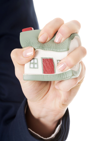 House model being squeezed in woman s hand  Over white background  Stok Fotoğraf