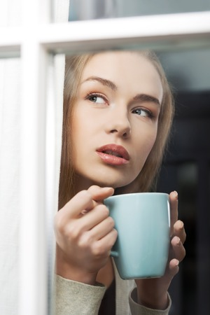 Beautiful caucasian woman drinking hot coffee or tea and looking through window. Indoor background.