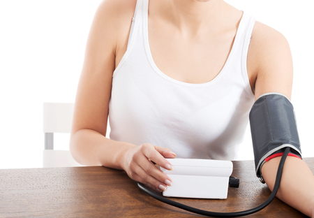 Mulher mede sua pressão arterial.