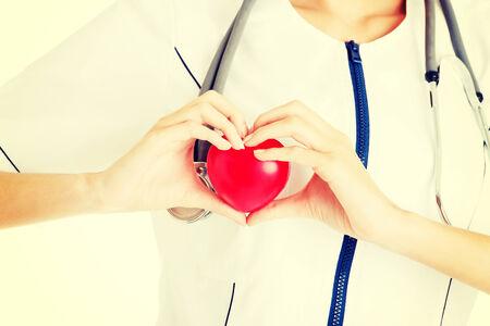 Giovane infermiera con il cuore in mano, isolato su bianco. Archivio Fotografico - 32186336
