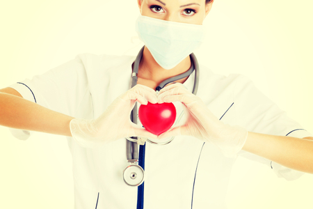 Giovane infermiera con il cuore in mano, isolato su bianco. Archivio Fotografico - 32928392