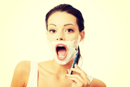 Beautiful young woman shaving her face with a razor Stock Photo - 32926054