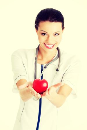Giovane infermiera con il cuore in mano, isolato su bianco. Archivio Fotografico - 32925478