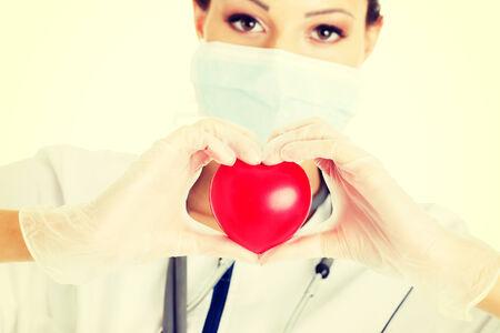 Giovane infermiera con il cuore in mano, isolato su bianco. Archivio Fotografico - 32925481