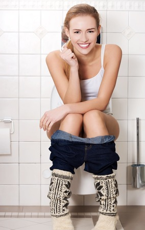 Young woman sitting on a toilet 版權商用圖片