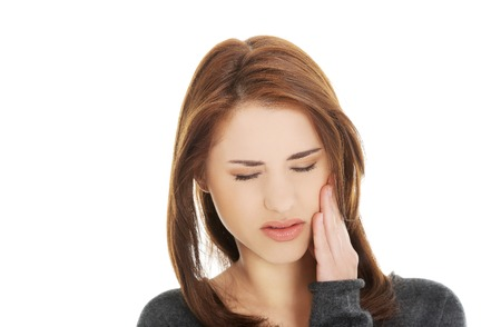 痛みを伴う表現で傷ついた頬を押すと 10 代女性 写真素材