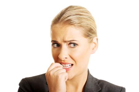Stressed jonge vrouw haar nagels bijten.