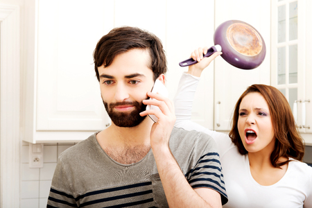 Young rage woman hitting her talking partner with frying pan. Archivio Fotografico