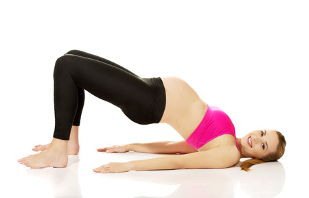 Calm pregnant woman exercising yoga.