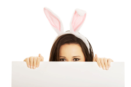 Happy woman wearing bunny ears and holding an empty baner