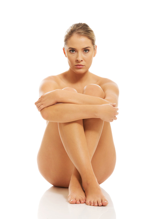 Nude woman sitting on the floor. Stock Photo