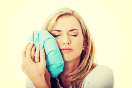 Woman heaving tooth ache, holding ice bag Banque d'images
