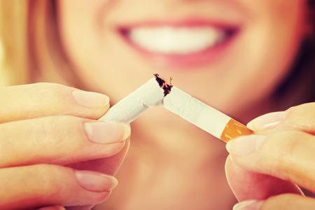 Jonge mooie vrouw die gebroken sigaret in de voorkant. Stockfoto
