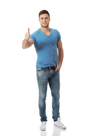 Happy young handsome man with thumbs up gesture. Standard-Bild