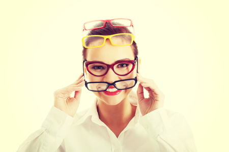 Beautiful young woman wearing four pair of glasses.