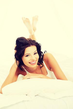Felice donna sensuale sdraiata sul letto.