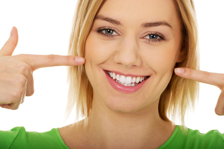 Beautiful woman pointing at toothy smile