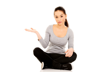 Young woman sitting cross legged with open hand. Stock Photo