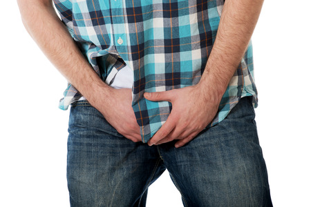 Young man holding his crotch because of pain. Foto de archivo