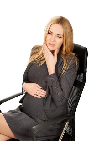 Zwangere vrouw in het kantoor met tandpijn Stockfoto