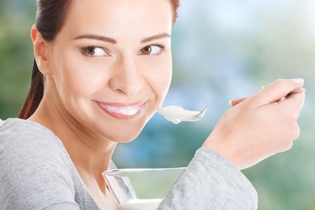 Healthy woman eating yoghurt with spoon.