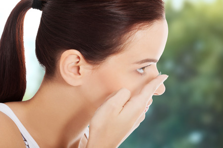 Woman applying contact lens in her eye. Foto de archivo