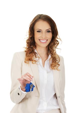 Businesswoman real estate agent giving keys.