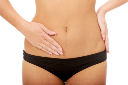 Woman in underwear touching her slim belly. Stock Photo