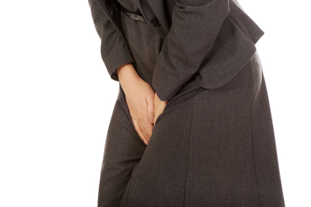 Businesswoman holding her painful crotch. Stock Photo