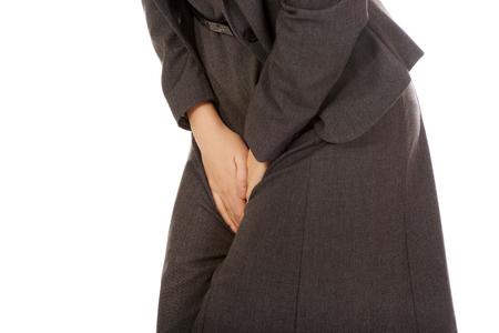 Businesswoman holding her painful crotch. Foto de archivo
