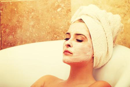 Mujer de relajación con los ojos cerrados y la loción de crema en la cara