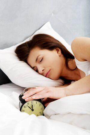 Mujer cansada y con sueño se apaga el despertador.