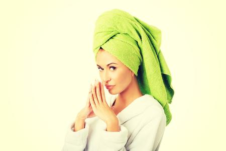Pensive woman in bathrobe and towel on head.