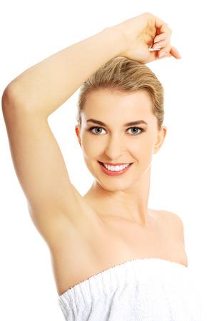 Beautiful happy spa woman showing her shaved armpit. Foto de archivo