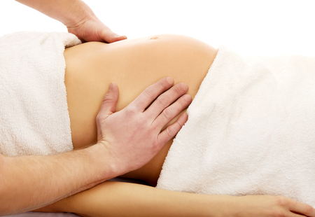 Pregnant woman having a massage on her belly Stock Photo